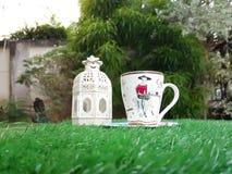 Taza de café con la linterna en hierba artificial verde Fotografía de archivo libre de regalías