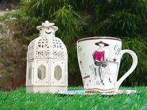 Taza de café con la linterna en hierba artificial verde Imágenes de archivo libres de regalías