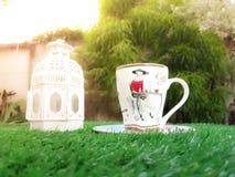 Taza de café con la linterna en hierba artificial verde Foto de archivo libre de regalías