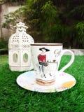 Taza de café con la linterna en hierba artificial verde Fotos de archivo