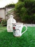Taza de café con la linterna en hierba artificial verde Imagen de archivo libre de regalías
