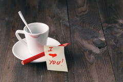 Taza de café con la marca del lápiz labial y nota y x27; amo el you& x27; en la tabla Imagenes de archivo