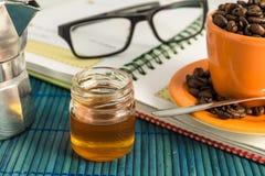 Taza de café con la miel, la lente y un moka Imágenes de archivo libres de regalías