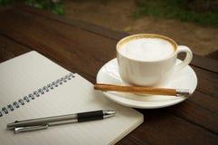 Taza de café con la pluma y el libro Imagen de archivo