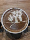 Taza de café con la sombra en la tabla de madera fotos de archivo