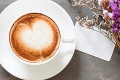 Taza de café con la tarjeta de presentación en fondo gris Imagenes de archivo