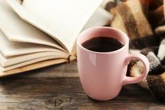 Taza de café con la tela escocesa y el libro en fondo de madera gris Foto de archivo libre de regalías