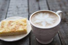 Taza de café con la torta en la tabla oscura Foto de archivo