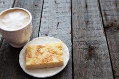 Taza de café con la torta en la tabla oscura Fotos de archivo