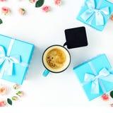 Taza de café con las cajas de regalo, rosas, muestra de madera negra Fotografía de archivo libre de regalías