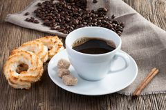 Taza de café con las galletas del coco, el canela y el azúcar de caña imagenes de archivo