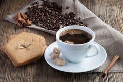 Taza de café con las galletas del pan de jengibre, el canela y el azúcar de caña fotografía de archivo libre de regalías