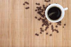 Taza de café con las habas en el fondo de bambú Imágenes de archivo libres de regalías
