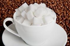 Taza de café con las habas y el azúcar de terrón Fotografía de archivo libre de regalías