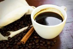 Taza de café con las habas y el palillo de canela. Foto de archivo libre de regalías