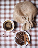 Taza de café con las habas y el saco en el mantel del top Foto de archivo