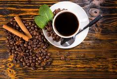 Taza de café con las habas y las especias asadas Foto de archivo