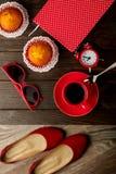 Taza de café con las magdalenas, la libreta, el despertador, los zapatos y el sol Imagenes de archivo