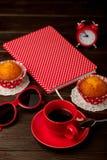 Taza de café con las magdalenas, la libreta, el despertador y las gafas de sol Imágenes de archivo libres de regalías
