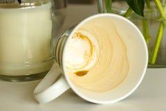 Taza de café con las rayas blancos y negros, mintiendo en la tabla Fotografía de archivo libre de regalías
