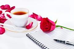 Taza de café con las rosas y el cuaderno rojos Foto de archivo libre de regalías