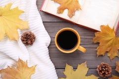 Taza de café con licencia de otoño y de libro viejo en fondo de madera fotos de archivo libres de regalías