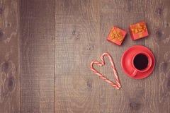 Taza de café con los bastones de caramelo y las cajas de regalo en la tabla de madera Visión desde arriba Foto de archivo