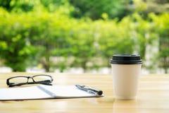 Taza de café con los glassess y de libreta en la tabla de madera sobre gre Foto de archivo libre de regalías