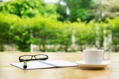 Taza de café con los glassess y de libreta en la tabla de madera sobre gre Foto de archivo