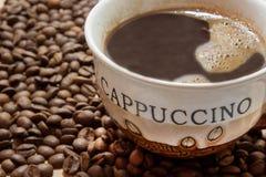 Taza de café con los granos de café Imagen de archivo