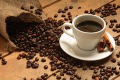 Taza de café con los granos de café cruasán, canela en el empaquetamiento y madera Fotos de archivo