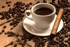 Taza de café con los granos de café, el cigarro en el empaquetamiento y la madera Imágenes de archivo libres de regalías