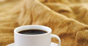 Taza de café con los granos de café en el saco almacen de metraje de vídeo
