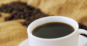 Taza de café con los granos de café en el saco metrajes
