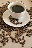 Taza de café con los granos de café en el saco del paño foto de archivo