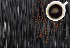 Taza de café con los granos de café en fondo negro Fotografía de archivo