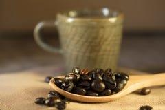 Taza de café con los granos de café en un fondo marrón hermoso Fotografía de archivo