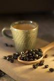 Taza de café con los granos de café en un fondo marrón hermoso Imágenes de archivo libres de regalías