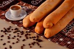 Taza de café con los granos de café y el baguette foto de archivo