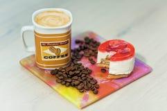 Taza de café con los granos de la torta y de café Taza de café con la torta Fotografía de archivo libre de regalías