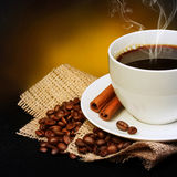 Taza de café con los granos del platillo y de café en la arpillera sobre negro Imágenes de archivo libres de regalías