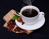 Taza de café con los granos del platillo y de café en la arpillera sobre negro Fotos de archivo libres de regalías