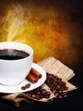 Taza de café con los granos del platillo y de café en la arpillera sobre oscuridad Imagen de archivo libre de regalías