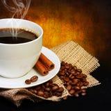 Taza de café con los granos del platillo y de café en la arpillera sobre oscuridad Foto de archivo libre de regalías