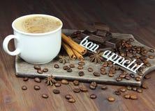 Taza de café con los granos, el chocolate, el canela, un anisetree y una inscripción Foto de archivo