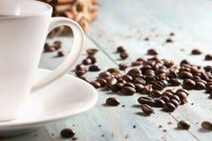 Taza de café con los granos de café en el primer de los tableros de madera Fotos de archivo
