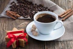 Taza de café con los granos, las galletas y el canela de café foto de archivo
