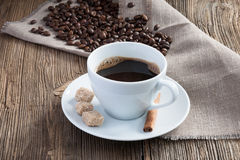 Taza de café con los granos y el cinamomo de café fotografía de archivo