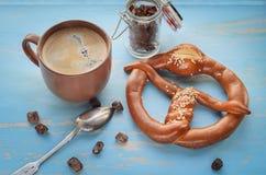 Taza de café con los granos y el pretzel de café Fotografía de archivo