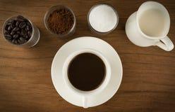 Taza de café con los ingredientes en los viejos tableros de madera Foto de archivo libre de regalías